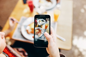 Person taking picture of food on their phone